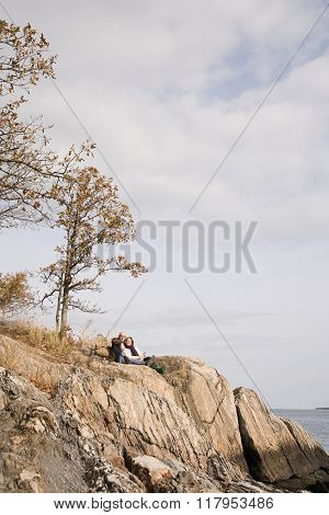 Mature couple resting on rocks
