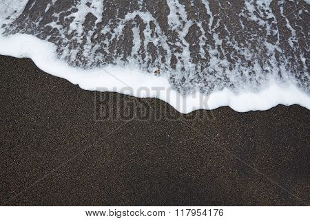 Black sand beach with wave foam texture in Fuerteventura at Canary Islands