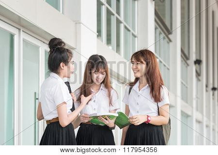 Group Of Asian Students In Uniform Studying Together At University