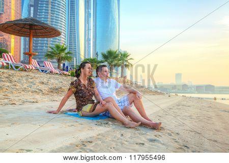 Couple watching romantic sunrise on the beach of Abu Dhabi