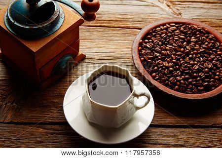 Coffee cup with vintage grinder on wooden old table