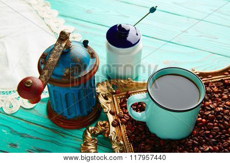 Coffee cup with vintage grinder on wooden old table and golden tray beans