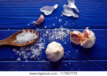 Garlic and salt spread on a blue wooden table with casual composition