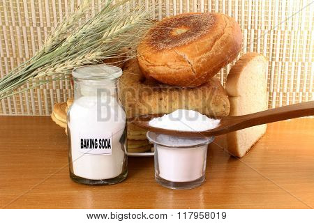 baking soda in a glass jar and wooden spoon with cookie and bread and wheat