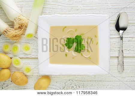 vichyssoise cream soup with leeks and potatoes on white wood table