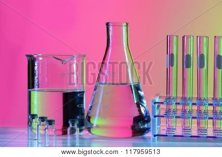 Laboratory glassware on reflective table over colorful background