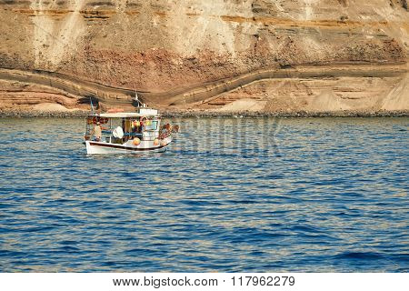 SANTORINI, GREECE - AUGUST 06, 2015: people on boat near Santorini sea coast. Santorini, classically Thera, and officially Thira, is an island in the southern Aegean Sea.