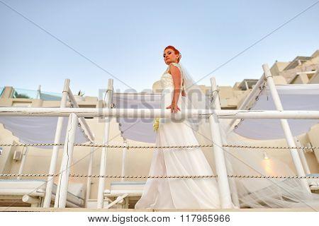 Pretty woman posing in white wedding dress on Santorini island, Greece