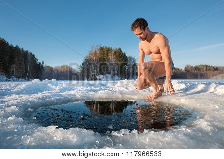 Young man going to swim in the winter lake in the ice hole