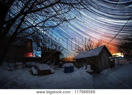 Winter garden and starry sky with star trails