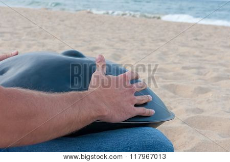 Man on the sand beach playing handpan or hang with sea On Background. The Hang is traditional ethnic