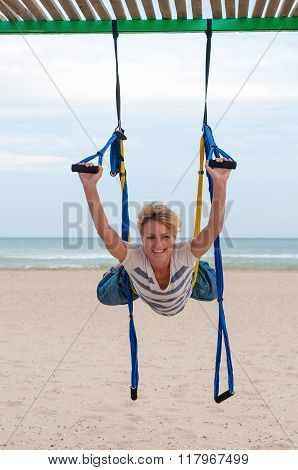 Young woman upside down doing anti-gravity aerial yoga or fly-yoga in hammock on sea background
