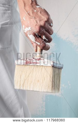 Workman Hand Holding Dirty Paintbrush