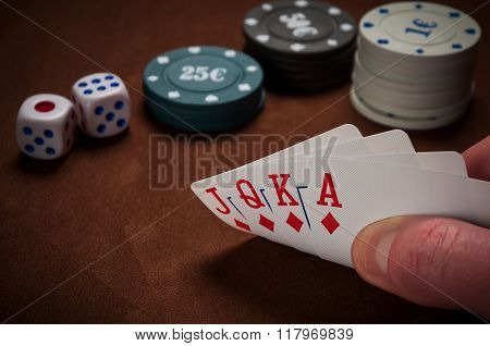 Chips And Cards For Poker In Hand On Table