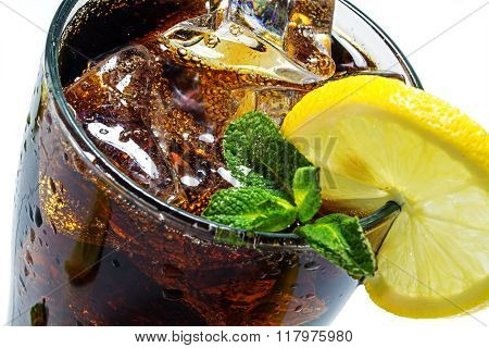 top of a glass of cola with ice cubes lemon slice and peppermint garnish