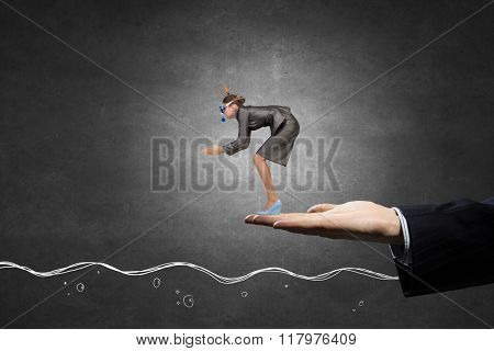 Businesswoman diving from palm