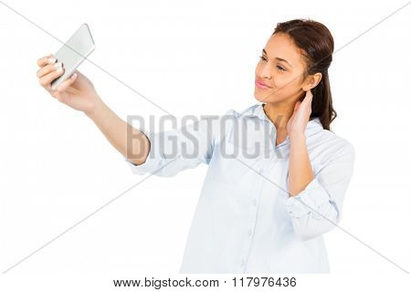 Casual smiling woman taking selfie on white background