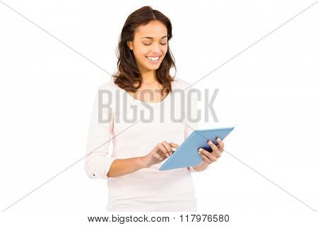 Casual smiling woman using tablet on white background
