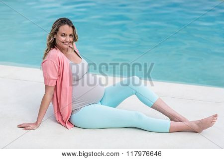 Pregnant woman relaxing outside next to the pool