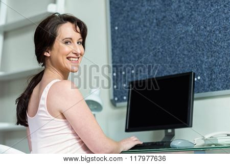 Pregnant woman on her computer at home