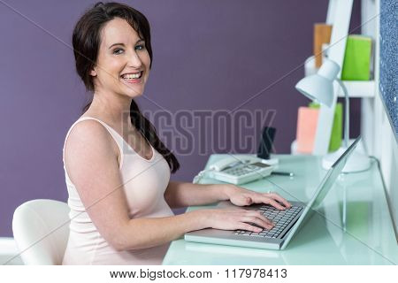 Pregnant woman on her laptop at home