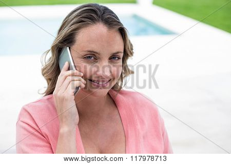 Pregnant woman making a phone call by the pool