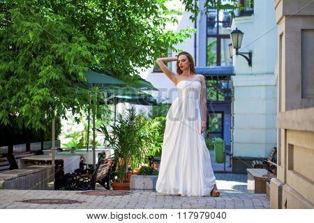 Full length portrait of beautiful model woman in white dress posing summer street