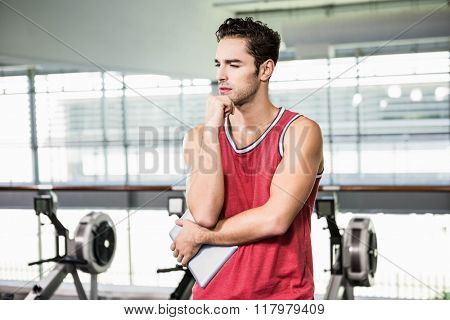 Thoughtful man with chin on fist in the gym