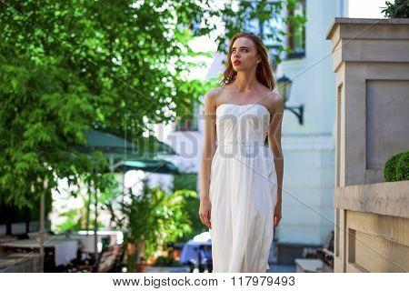 Portrait of beautiful model woman in wearing white dress posing summer street
