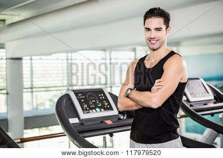 Smiling man on treadmill standing with arms crossed at the gym