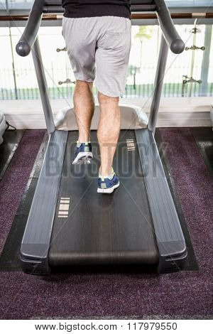 Lower section of fit man running on treadmill at the gym