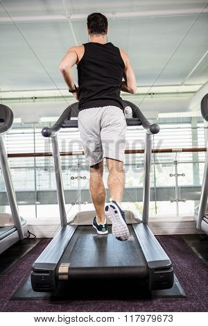 Fit man running on treadmill at the gym