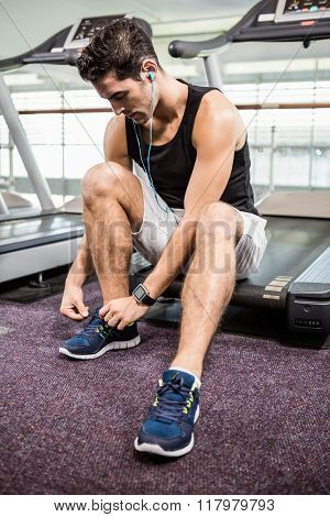 Fit man sitting on treadmill and tying the shoelace at the gym