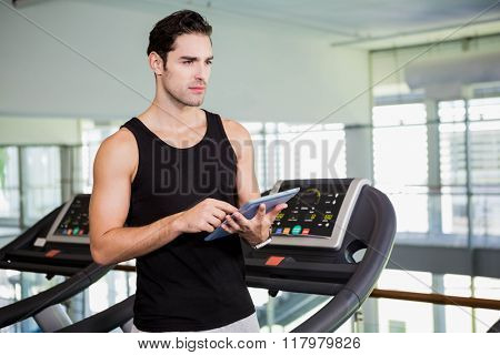 Serious man on treadmill standing with tablet at the gym