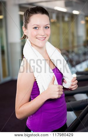 Smiling fit woman with towel around her neck standing in the gym