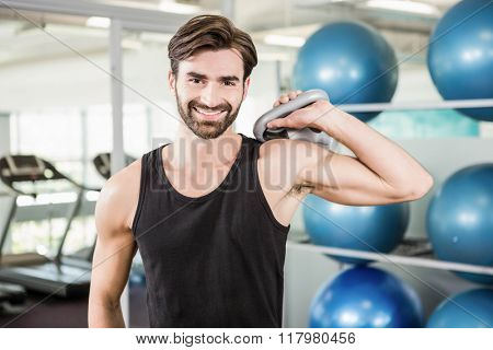 Concentrated man lifting kettlebell in the studio