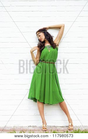 Beautiful young woman in green dress, against white wall