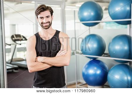 Smiling man standing with arms crossed in the gym