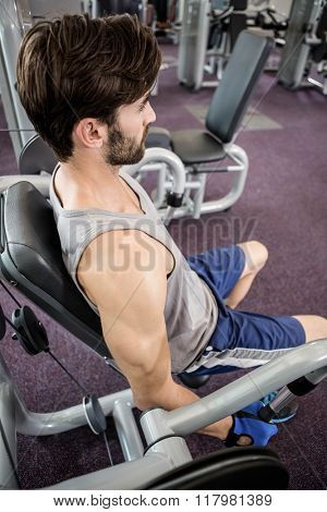 Focused man using weights machine for arms at the gym