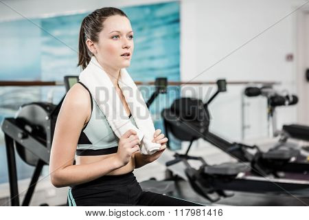 Tired woman with towel around neck at the gym