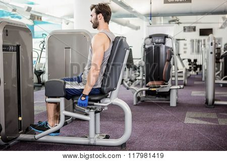 Focused man using weights machine for legs at the gym