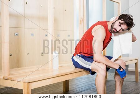 Tired man wiping sweat with towel in locker room