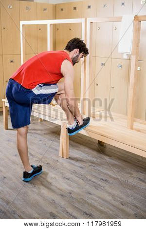 Man tying shoelace in locker room at the gym