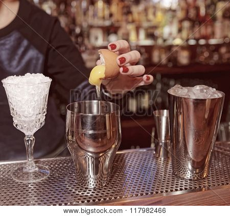 Female bartender is adding egg yolk to the glass, toned