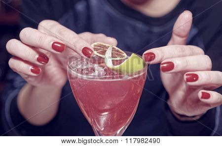 Female bartender is adding citrus zest to cocktail, toned image