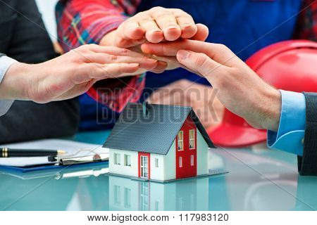 Hands as a protecting roof over a little house