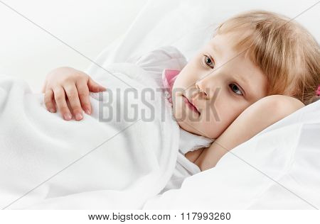 pensive Girl lying in white bed
