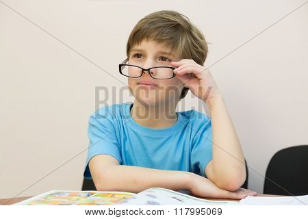 One little boy is taking off glasses and sitting at the table.