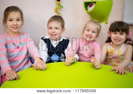 Four little girls and boy are sitting at the table and holding hands.