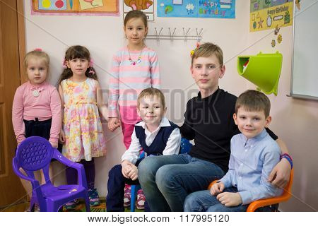 Three boys are sitting on the arm-chair and three girls are standing near the wall.